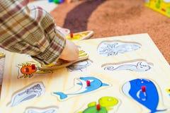 Det lilla barnet sätter det enkla pusslet på golvet Arkivfoton