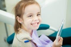 Det lilla barnet ser tänder för snöig vit i spegel royaltyfri foto