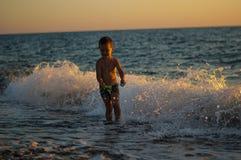Det lilla barnet spelar med vatten wave Strand arkivfoto