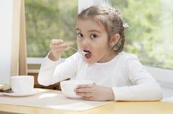 Det lilla barnet äter yoghurt Arkivfoton