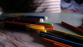 Det lilla barnet väljer kulöra tuschpennor och ritar på tabellen hemma på ett stycke av papper i mörkret stock video