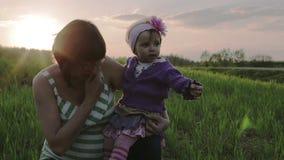 Det lilla dottersammanträdet på varven av modern på solnedgången stock video