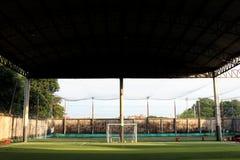 Det lilla fotbollfältet, Futsal bollfält i idrottshallen inomhus, det utomhus- fotbollsportfältet parkerar med konstgjord torva Arkivbild