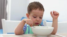 Det lilla gulliga barnet sitter på en tabell och äter hans egen havremjöl, behandla som ett barn äter gärna Lycklig barndom för b stock video