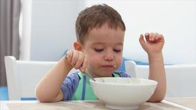 Det lilla gulliga barnet sitter p? en tabell och ?ter hans egen havremj?l, behandla som ett barn ?ter g?rna Lycklig barndom f?r b stock video