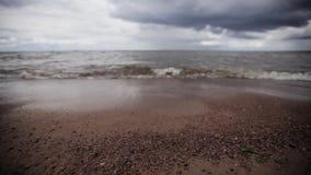 Det lilla havet vinkar på stranden med mycket små stenar Grå färgmolnhimmel Sommar Glidarepanna lager videofilmer