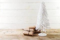 Det lilla julträdet från vit flockades tråd och gåvor i kraft arkivbild