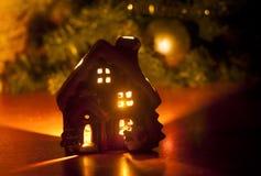 Det lilla leksakjulhuset med en brinnande ljusinsida är på tabellen nära julgranen Royaltyfri Bild