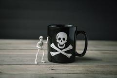 Det lilla skelett- anseendet bredvid kaffe rånar royaltyfri fotografi