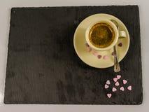 Det lilla svarta kaffet i en kopp, spillda söta purpurfärgade hjärtor, bl Arkivbilder