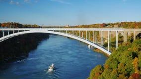 Det lilla vita skeppet seglar under bron över floden Niagara Något av det populära Niagaraet Falls i USA arkivfilmer