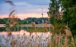 Det litauiska landskapet av sjön och tv står högt synligt royaltyfri bild