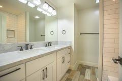 Det ljusa öppna badrummet för vitt ljus med marmorräknare och trägolvet i fastighet för San Diego modellhem skjuter royaltyfri fotografi