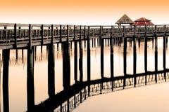 Det ljusa reflekterande vattnet för gammal träbroafton Arkivfoto