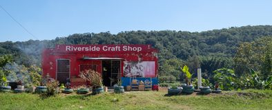 Det ljust färgade hantverket shoppar 'flodstrandhantverket shoppar 'i landsbygd i de Drakensberg bergen, Sydafrika arkivfoton