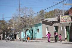 Det lokala folket går i en gata av Uyuni, Bolivia Arkivfoton