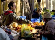 det lokala folket köper nya grönsaker och frukter på den lokala marknaden Arkivbild