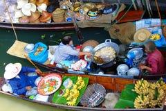 Det lokala folket säljer frukter, mat och produkter på Damnoen Saduak som svävar marknaden Royaltyfri Foto