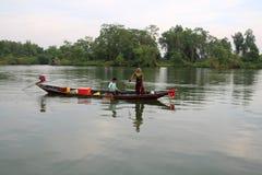 Det lokala folket som fiskar på ett litet fartyg på kanalen Royaltyfria Bilder