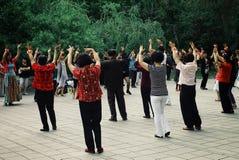 det lokala folket som har en övning för danstai-chi i ett offentligt, parkerar trädgården arkivbilder