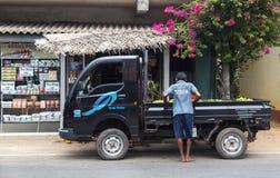 Det lokala mananseendet vid den svarta lastbilen som parkeras av teet, shoppar framme. Arkivfoton
