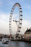 Det London ögat från den Westminster bron på mot en blå himmel med det turist- fartyget i förgrunden Royaltyfria Bilder