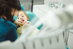 Det lugna barnet i tand- kontor låter tandläkaren undersöka tänder Pojken behandlas för karies royaltyfri foto