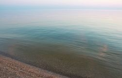 Det lugna blåa havet på solnedgången Royaltyfria Bilder