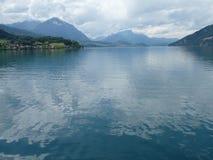 Det lugna blått-gräsplan vattnet av Thunersee, Schweiz Arkivbild