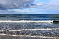 Det lugna havet vinkar tvätta kusten Arkivbild