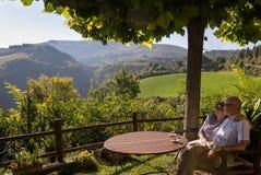 Det lyckliga åldringparet beundrar sikt av Tuscany Arkivfoto