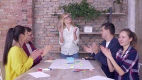 Det lyckliga affärsfolket gratulerar den företags ledaren på födelsedag- och applådhänder, medan arbeta på ny utveckling stock video
