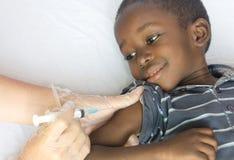 Det lyckliga afrikanska barnet får en visarinjektion från en vit volontärdoktor arkivfoto
