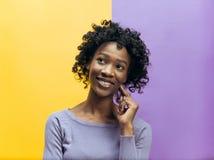 Det lyckliga afrikanska kvinnaanseendet och le mot grå bakgrund arkivbild