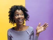 Det lyckliga afrikanska kvinnaanseendet och le mot grå bakgrund fotografering för bildbyråer