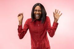 Det lyckliga afrikanska kvinnaanseendet och le mot röd bakgrund arkivfoto