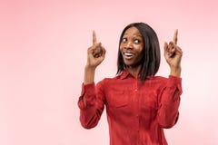 Det lyckliga afrikanska kvinnaanseendet och le mot röd bakgrund arkivbild