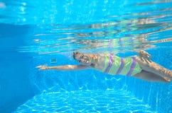 Det lyckliga aktiva barnet simmar fristil i pöl, undervattens- sikt Arkivfoton