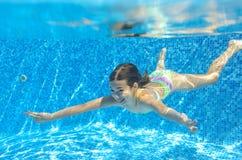 Det lyckliga aktiva barnet simmar undervattens- i pöl Arkivfoto