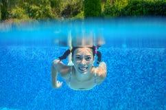 Det lyckliga aktiva undervattens- barnet simmar i pöl Arkivbilder