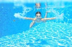 Det lyckliga aktiva undervattens- barnet simmar i pölen, härlig sund flickasimning Arkivfoto