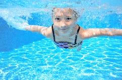 Det lyckliga aktiva undervattens- barnet simmar i pölen, härlig sund flickasimning arkivfoton