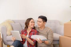 Det lyckliga asiatiska paret som väljer väggen, färgar för nytt hem royaltyfri fotografi