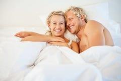 Det lyckliga barn kopplar ihop i säng Arkivbilder
