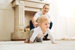 Det lyckliga barnet avlar att se hans behandla som ett barn krypning och att le glatt Arkivbilder