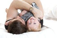 Det lyckliga barnet avlar och den lilla sonen som spelar på säng Royaltyfria Bilder