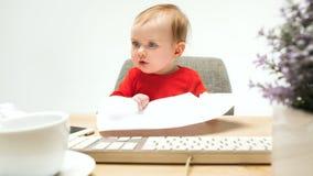Det lyckliga barnet behandla som ett barn flickalitet barnsammanträde med tangentbordet av datoren som isoleras på en vit bakgrun Arkivfoto