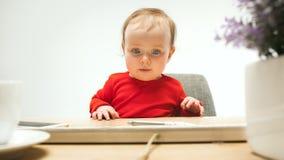 Det lyckliga barnet behandla som ett barn flickalitet barnsammanträde med tangentbordet av datoren som isoleras på en vit bakgrun Arkivfoton