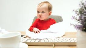 Det lyckliga barnet behandla som ett barn flickalitet barnsammanträde med tangentbordet av datoren som isoleras på en vit bakgrun Arkivbild