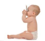 Det lyckliga barnet behandla som ett barn litet barnsammanträde som ler kyssande mobil cellphon Royaltyfri Fotografi
